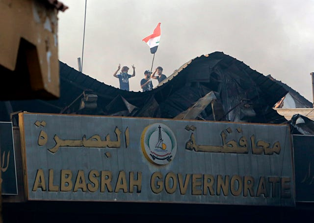 Protesters raise the Iraqi flag over the Basra government building