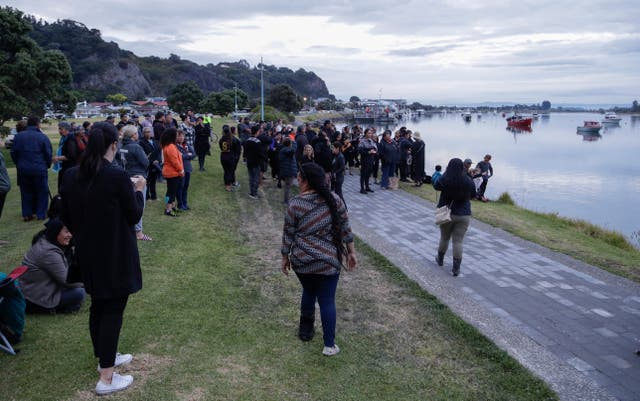 Locals on the beach a Whakatane beach as they await the recovery of victims (Mark Baker/AP)