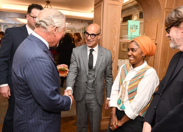 The Prince of Wales shakes hands with Stanley Tucci, watched by Nadiya Hussain