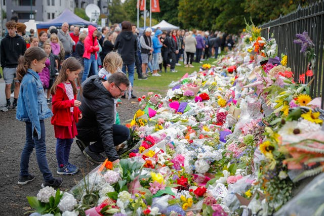Mourners lay flowers on a wall at the Botanical Gardens in Christchurch