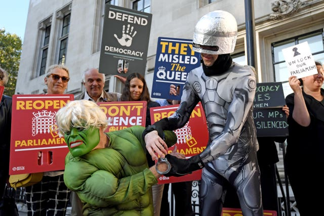 Protesters dressed as the Incredible Hulk and Robocop outside the Supreme Court in London