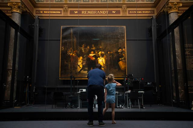 A limited amount of visitors admire Rembrandt's Night Watch  (Peter Dejong/AP)