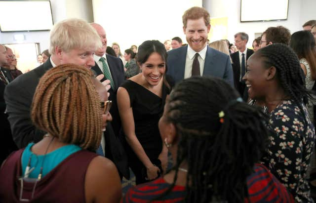 Foreign Secretary Boris Johnson, Prince Harry and Meghan Markle speak to guests at a women's empowerment reception (Chris Jackson/PA)