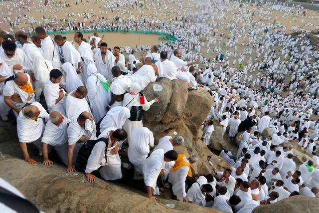 Muslim pilgrims make their way down a rocky hill known as the Mountain of Mercy, on the Plain of Arafat, during the annual hajj pilgrimage, near the holy city of Mecca, Saudi Arabia