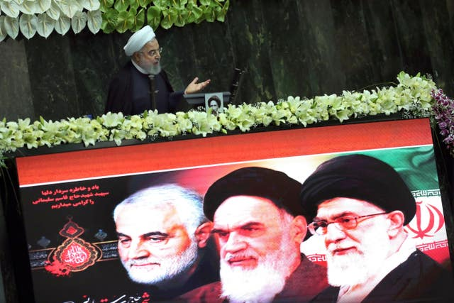 Iranian President Hassan Rouhani speaks during the inauguration of the new parliament, as a screen shows portraits of the Supreme Leader Ayatollah Ali Khamenei, right, late revolutionary founder Ayatollah Khomeini, centre, and Gen. Qassem Soleimani, who was killed in Iraq in a US drone attack (Vahid Salemi/AP)