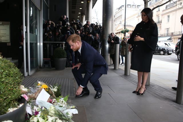The Duke of Sussex leaves flowers, watched by the Duchess of Sussex, as they arrive at New Zealand House in London