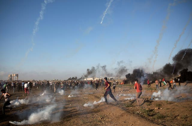 Protesters escape from teargas fired by Israeli troops