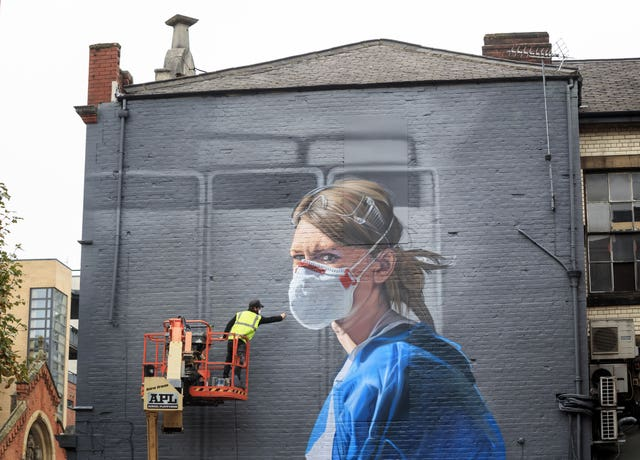 Artist Peter Barber works on a mural in Manchester city centre of Johannah Churchill 's photograph. Danny Lawson/PA Wire