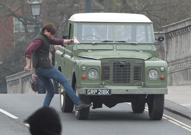 Domhnall Gleeson kicking a car during filming