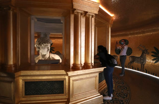 Visitors take photos of the 3D reproduction of Michelangelo's David