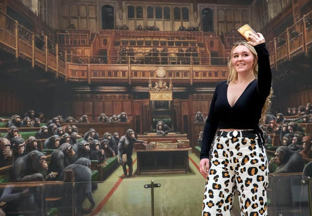 Isabelle Schofield takes a photo of herself in front of the painting 'Devolved Parliament' at Bristol Museum (Steve Parsons/PA)