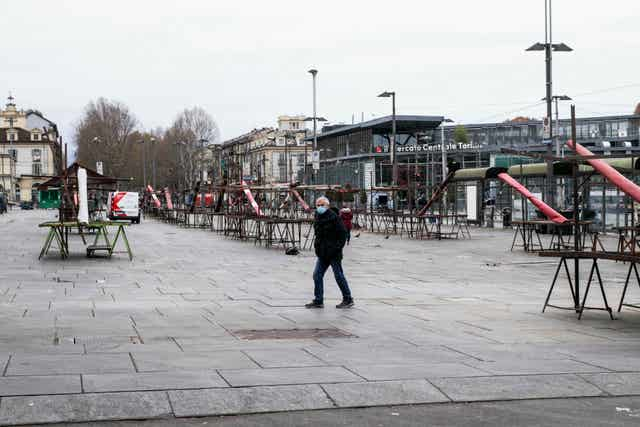 A man walks in the empty Porta Palazzo open market in Turin, Italy