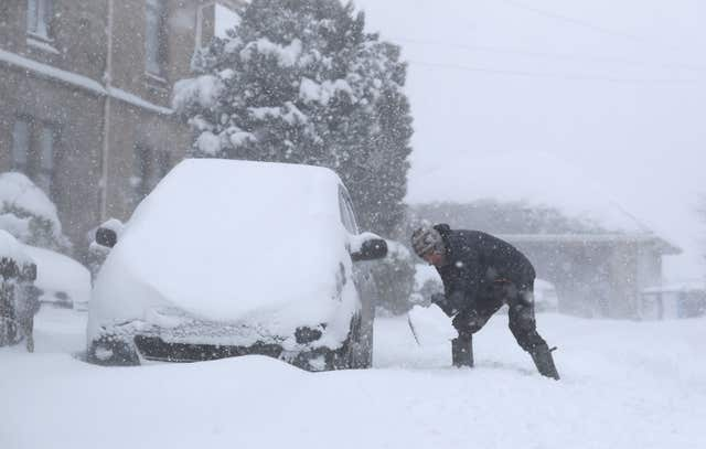A man tries to dig his car out of snow