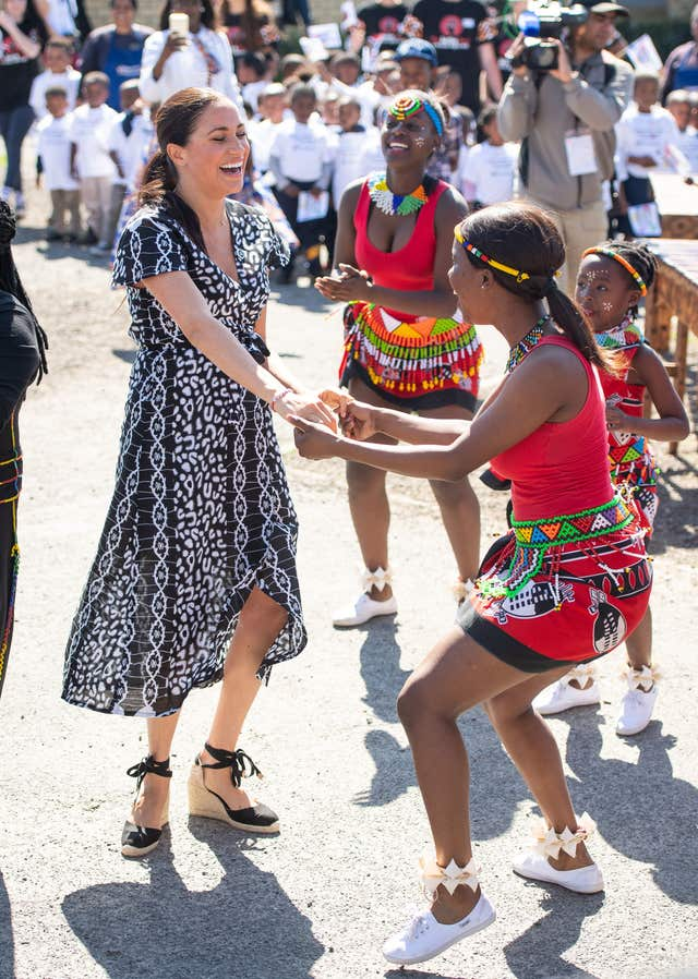 The Duchess of Sussex joins in with dancers as she leaves the Nyanga Township in Cape Town, South Africa, on the first day of their tour of Africa