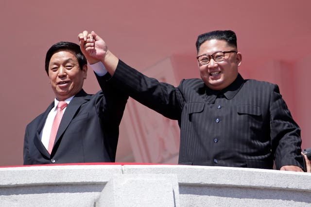 Kim Jong Un raises hands with China's third highest ranking official, Li Zhanshu