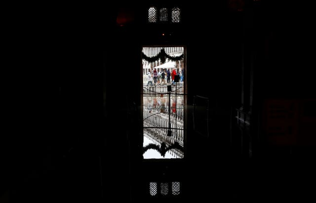 People are reflected in floodwater at the entrance inside St Mark's Basilica in Venice, Italy