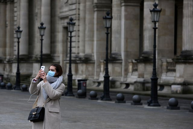 A tourist wearing a mask outside the Louvre