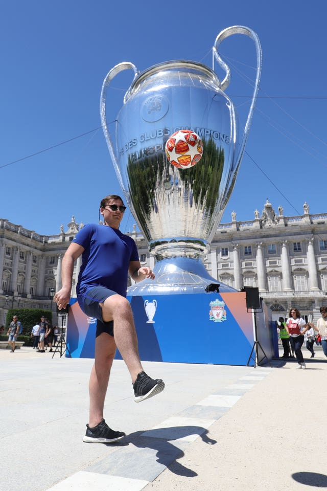 A man kicks a ball in front of an inflatable Champions League cup in Plaza Mayor in Madrid