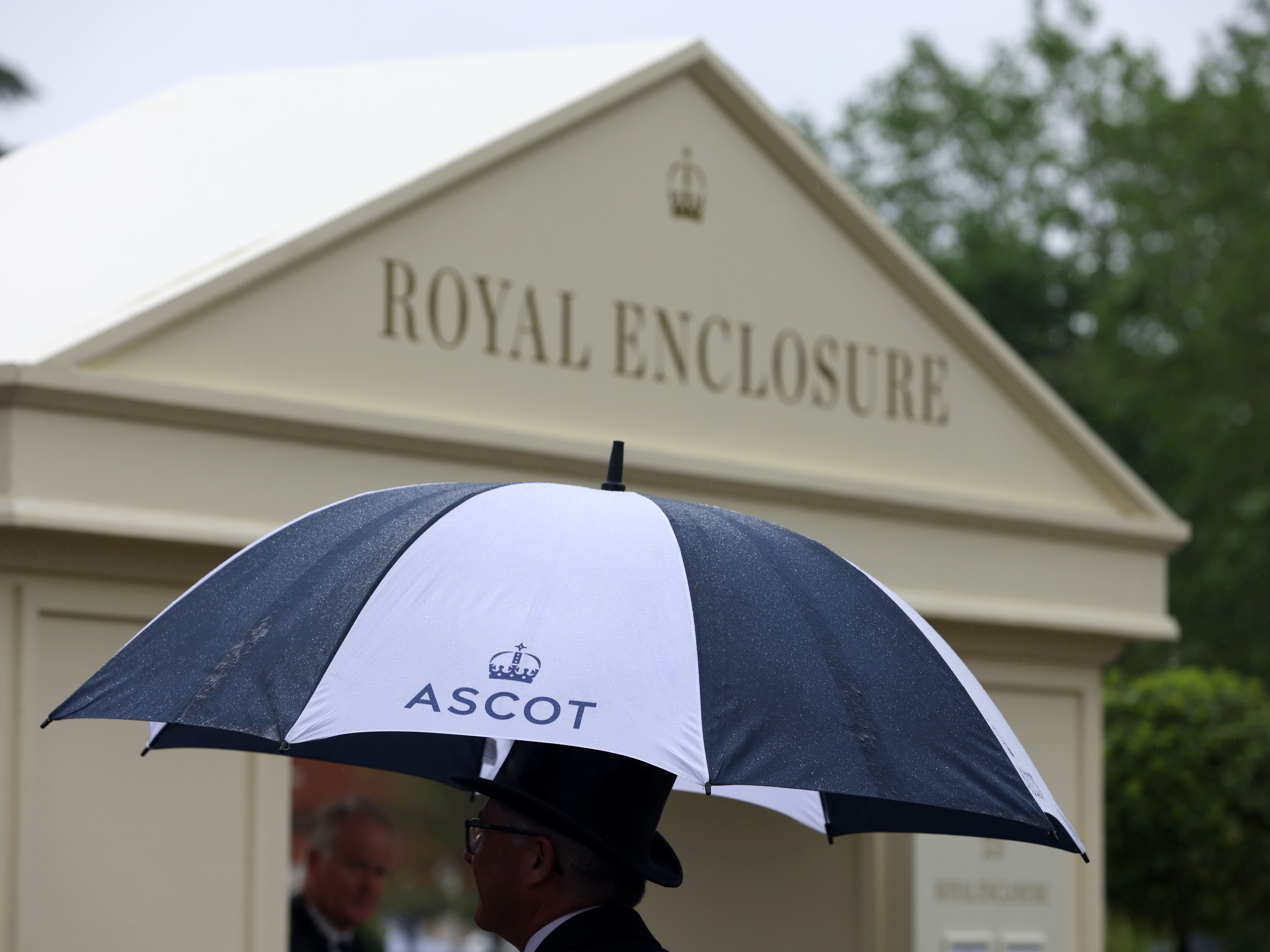 A racegoer takes cover from the heavy rain under an umbrella during day four of Royal Ascot (Steven Paston/PA)