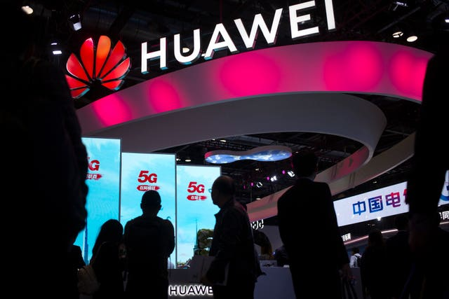 Attendees walk past a display for 5G services from Chinese technology firm Huawei at the PT Expo in Beijing