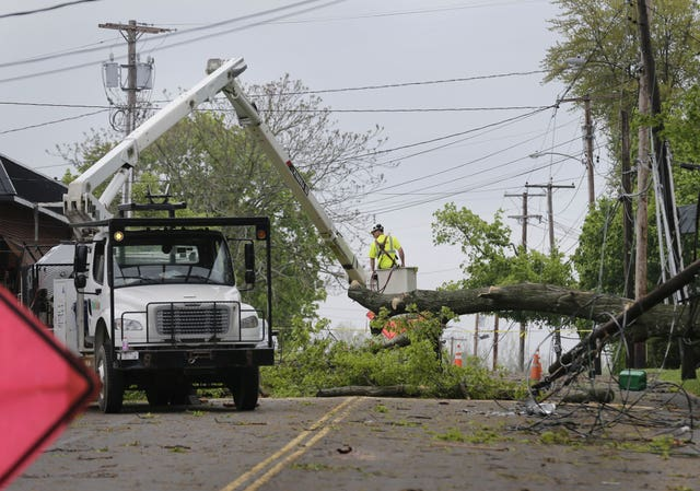 A utility crew works to clear a roadway of storm debris in New York (AP)