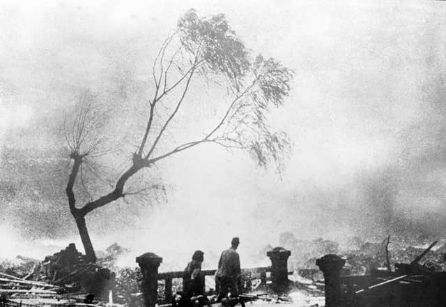 Survivors of the atomic bomb attack of Nagasaki, Japan, walk through the destruction as fire rages in the background