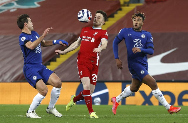 Liverpool forward Diogo Jota controls the ball on his chest as he is challenged by Chelsea's Reece James and Cesar Azpilicueta