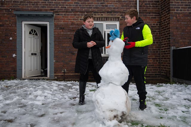 Teenage brothers build snowman