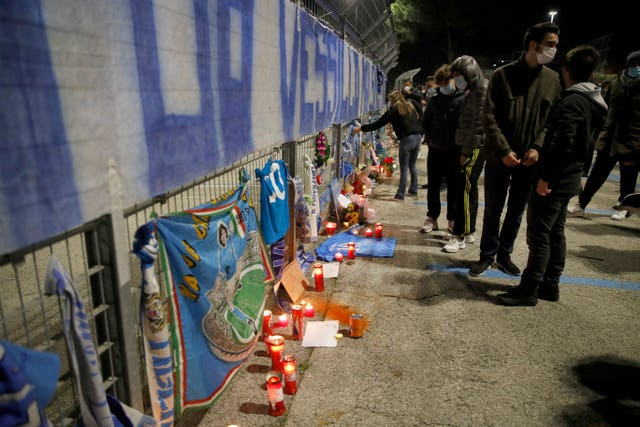 People lay flowers and light candles as they gather outside the San Paolo Stadium