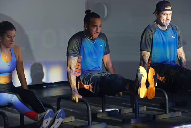 Hamilton, centre, exercises during a promotional event in Mexico City