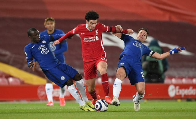 Curtis Jones evades tackles from two Chelsea players