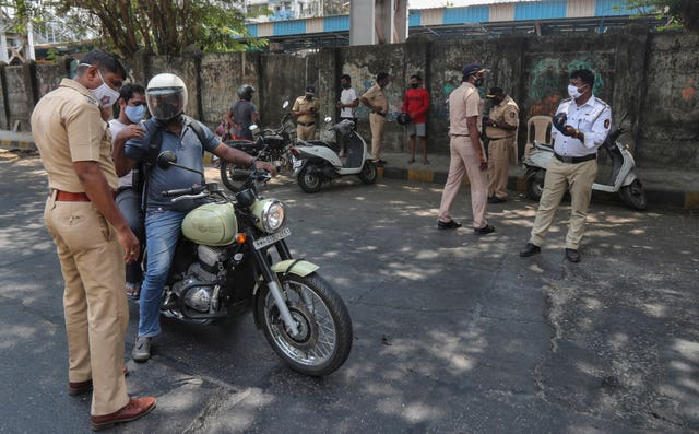 A police officer stops a commuter during restrictions in Mumbai , India