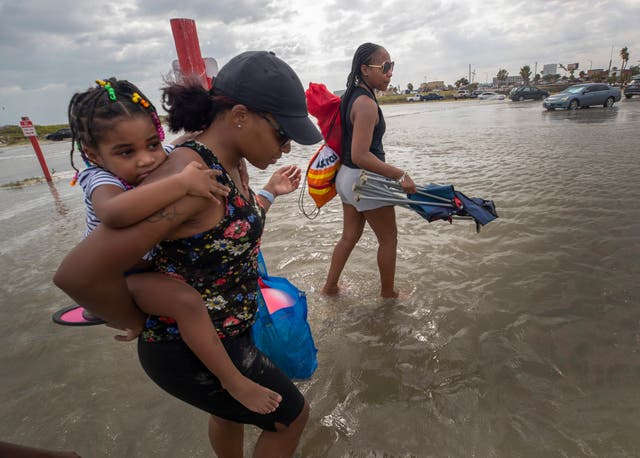 A woman gives her daughter a piggyback ride across a flooded area