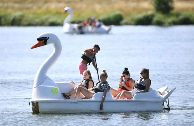 People on pedalos and paddleboards at Nene Park in Peterborough