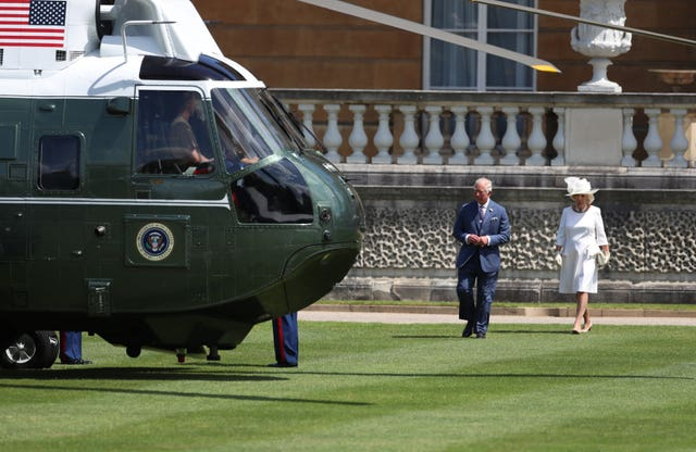 The Prince of Wales and the Duchess of Cornwall wait to meet US President Donald Trump and his wife Melania as they arrive in Marine One at Buckingham Palace