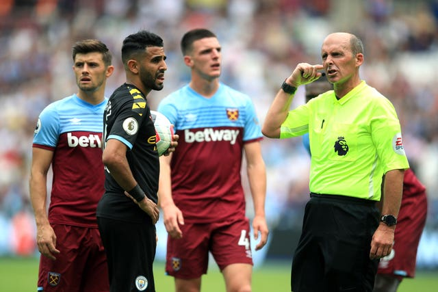 Referee Mike Dean, right, awaits the VAR's verdict as Declan Rice looks on