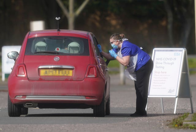 An NHS worker is tested for coronavirus at a temporary drive-through testing station in the car park of Chessington World of Adventures