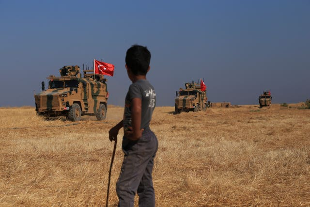 Turkish armoured vehicles conduct a joint ground patrol with American forces in the so-called 'safe zone' on the Syrian side of the border with Turkey