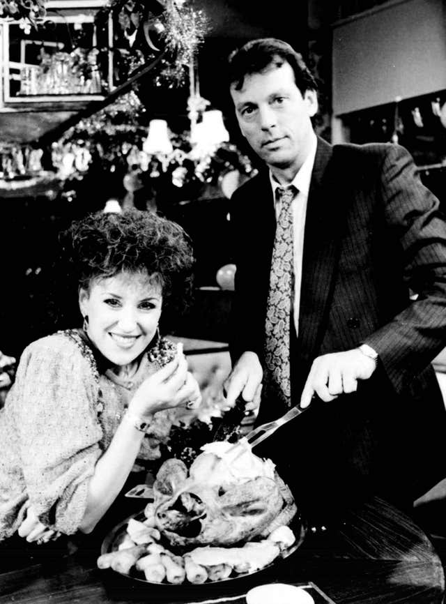 Queen Vic landlord Den Watts (Leslie Grantham) and on-screen wife Angie (Anita Dobson) carving the Christmas turkey (PA)