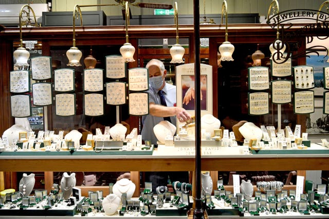A jeweller removes jewellery from his window