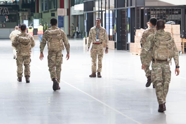 Soldiers and private contractors help to prepare the ExCel centre, London, as it was being made into the temporary NHS Nightingale hospital (Stefan Rousseau/PA)