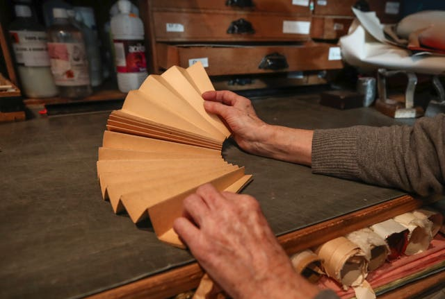 Anne Hoguet, 74, fan-maker and director of the hand fan-making museum unfolds a mounting fan in her workshop
