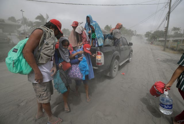 A family evacuates to safer grounds as Taal volcano in Tagaytay, Cavite province, southern Philippines