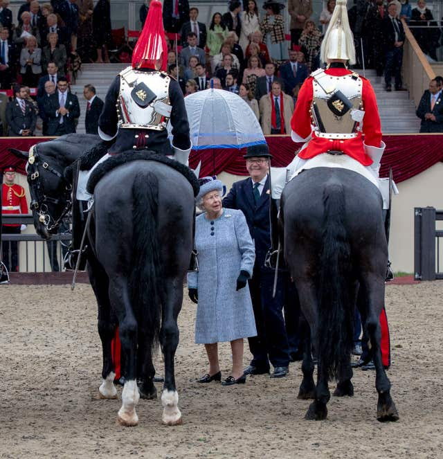 The Queen presents the award to the best turned out trooper of the Household Cavalry (Steve Parsons/PA)