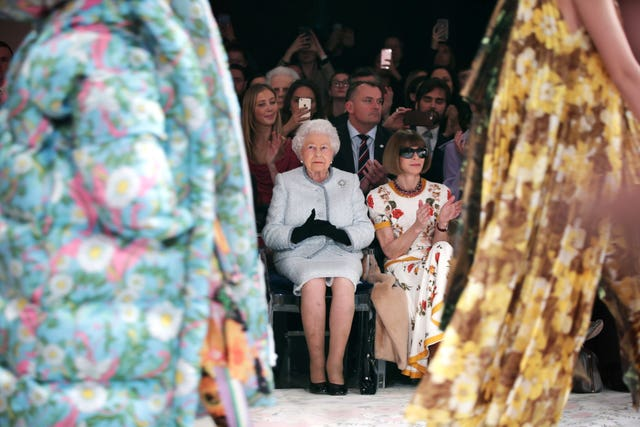 The Queen sitting next to Anna Wintour as they view Richard Quinn's runway show at London Fashion Week