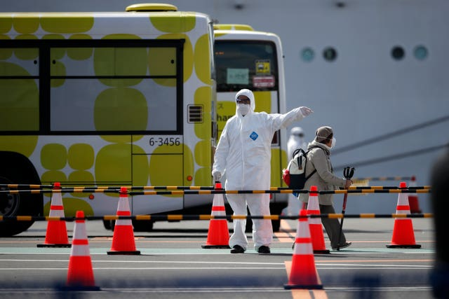 A passenger is directed in a car park after disembarking from the quarantined Diamond Princess cruise ship in Yokohama, near Tokyo