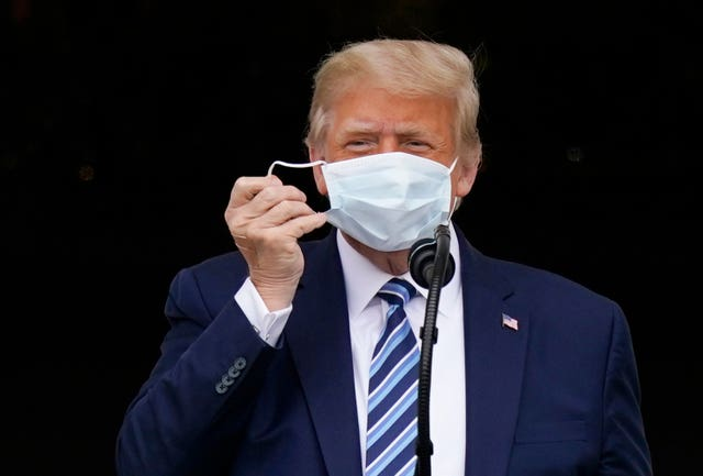 With two bandages on his hand, President Donald Trump removes his face mask