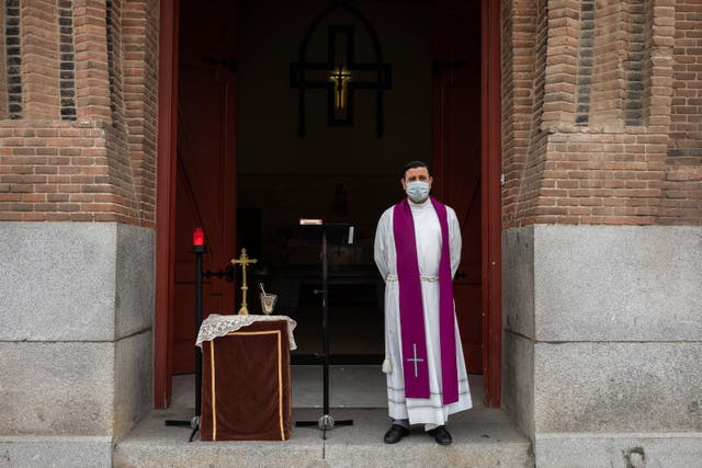 A priest wearing a face mask to protect against coronavirus waits in front of the cemetery chapel during the coronavirus outbreak in Madrid, Spain