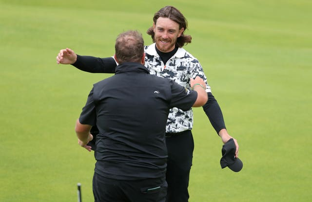 Shane Lowry, left, and England's Tommy Fleetwood embrace on the 18th