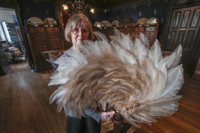 Anne Hoguet, 74, fan-maker and director of the hand fan-making museum poses with a feather fan at the museum in Paris